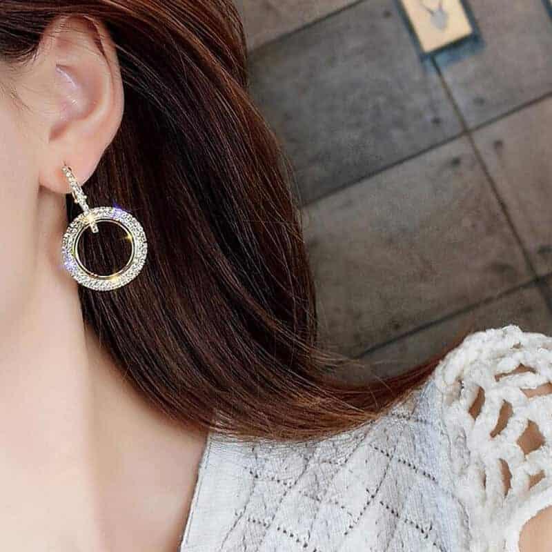 uhani srebrni moderni na ušesu ženske