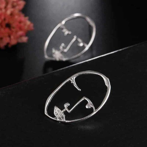 ženski srebrni uhani vzorec dekliški obraz umetnost in moda