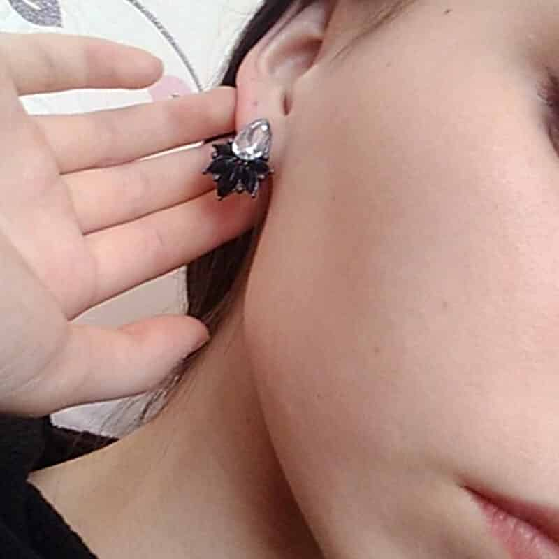 kristalni uhani črne barve z velikim diamantom na ženskem ušesu