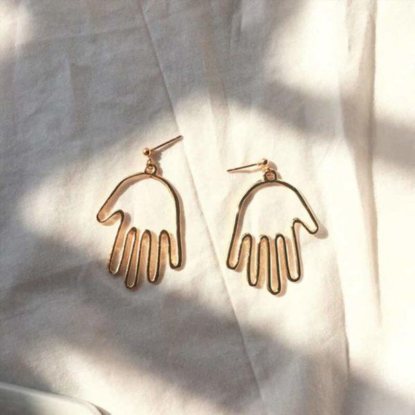 zlati viseči uhani v obliki roke