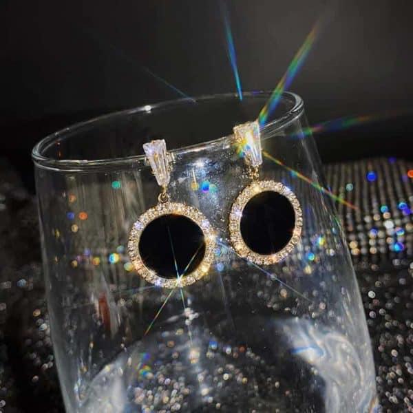 nakitko uhani zlate barve s črnim krogom